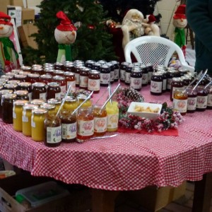 Jars of Norfolk Garden jams and chutneys being tasted at Christmas craft fair 2014